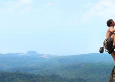 un homme grimpe une falaise avec un arrière plan montagneux