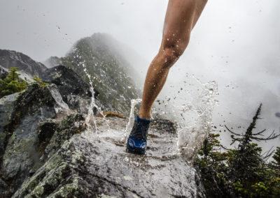 Un homme court sur une arête rocheuse mouillée