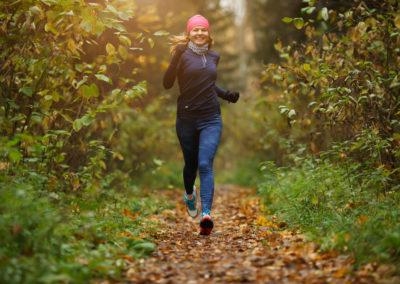 Une jeune femme blonde court sur un sentier forestier