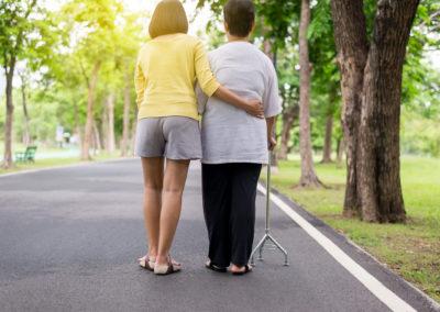 Une personne aide à personne hémiplégique à marcher
