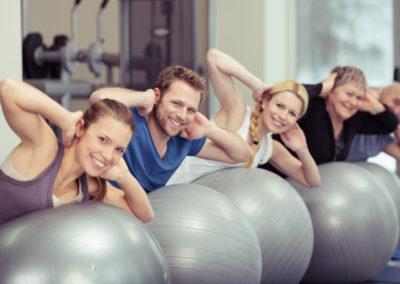 un groupe de personnes de tous âges pratique le Pilates avec de gros ballons