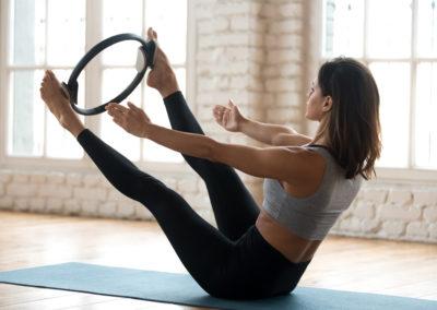 une jeune femme pratique un exercice de Pilates appelé teaser avec un cercle tenu entre les chevilles